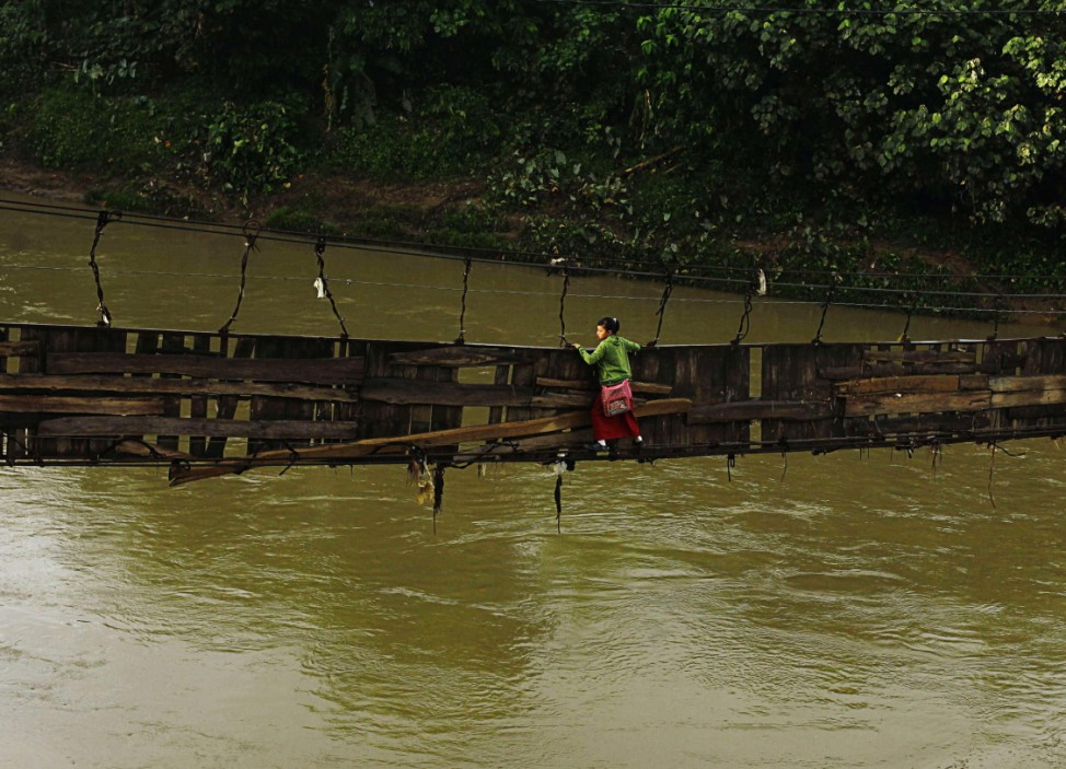 A student holds on to side steel bars of collapsed bridge as she crosses river to get to school at Sanghiang Tanjung village in Lebak regency