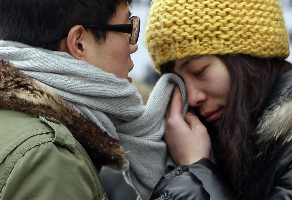 A woman wipes her tears with her partner's scarf as they part at Beijing west railway station