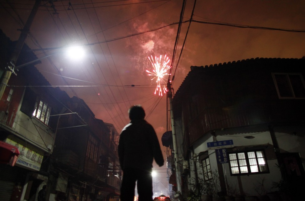A boy watches fireworks as part of Chinese new year celebrations in Shanghai