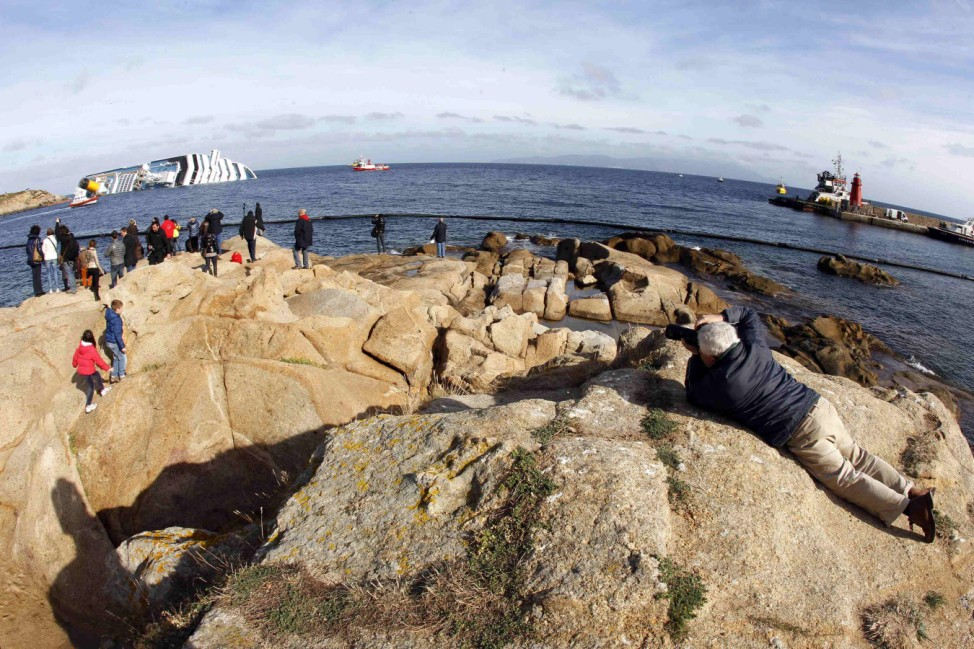 People look from a rock in front of the Costa Concordia cruise ship which ran aground off the west coast of Italy at Giglio island