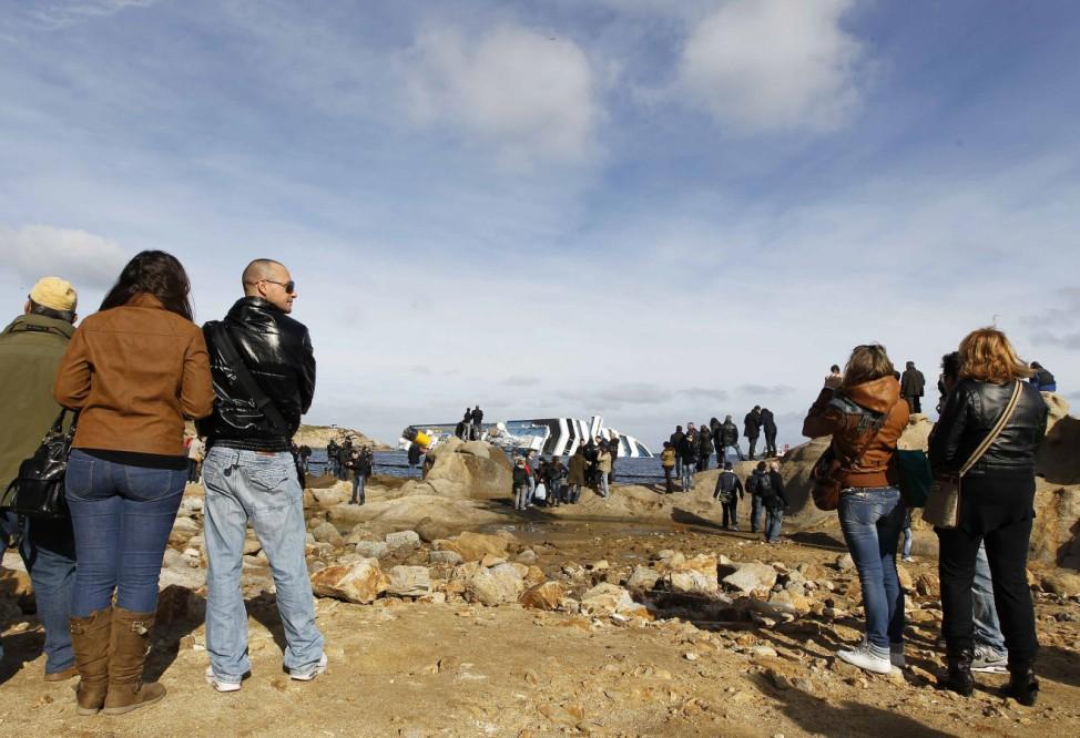 Tourists watch the Costa Concordia cruise ship on Giglio Island