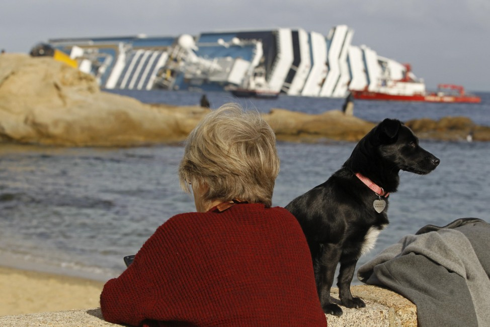 A woman and her dog stand on the dock near the Costa Concordia cruise ship at Giglio Island