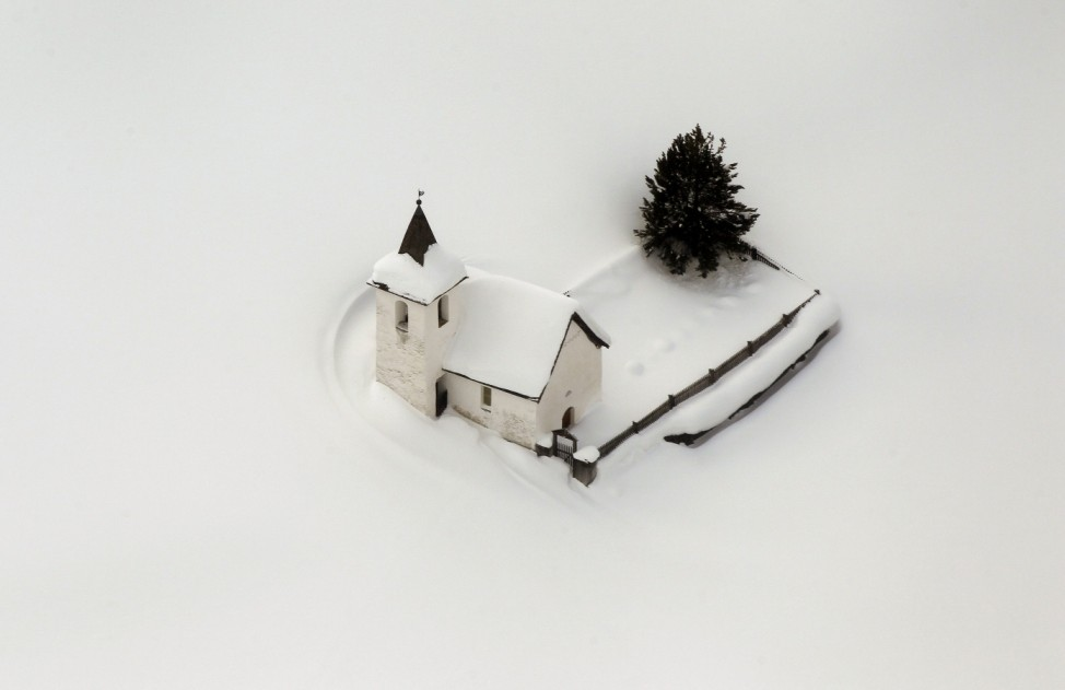 An aerial view shows the snow covered church of the village of Jenisberg near Davos