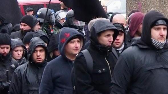 """Rechtsradikale spielen """"Paulchen Panther"""": Neonazis bei einer Demonstration in München am Samstag. Die Fahnenstangen könnten auch als Knüppel verwendet werden."""
