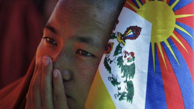 A Tibetan monk holds a flag as he takes part in a day-long hunger strike in New Delhi