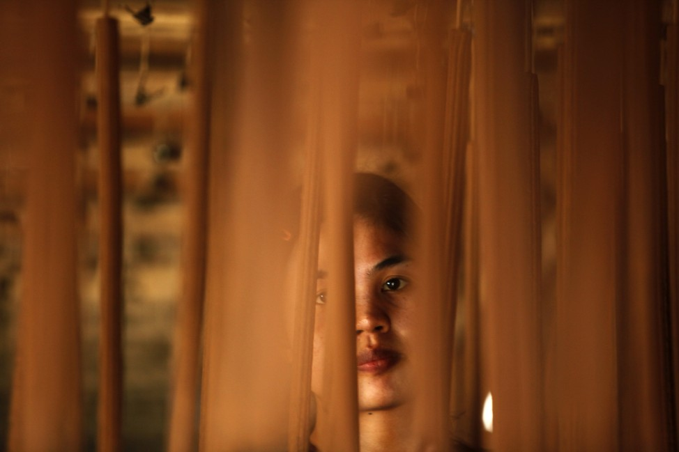 A worker looks through incense sticks during a drying process ahead of the Chinese Lunar New Year at an incense factory in Tangerang