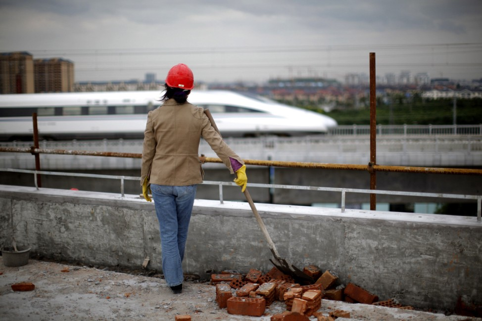 A worker watches train pass on new high-speed railway line between Shanghai and Hangzhou on the outskirts of Shanghai