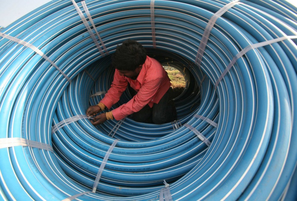 A labourer works amid rolls of underground telephone cable pipes on the outskirts of Jammu