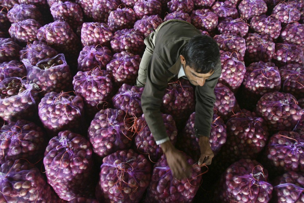 A worker packs onion bags at a wholesale vegetable market in Chandigarh