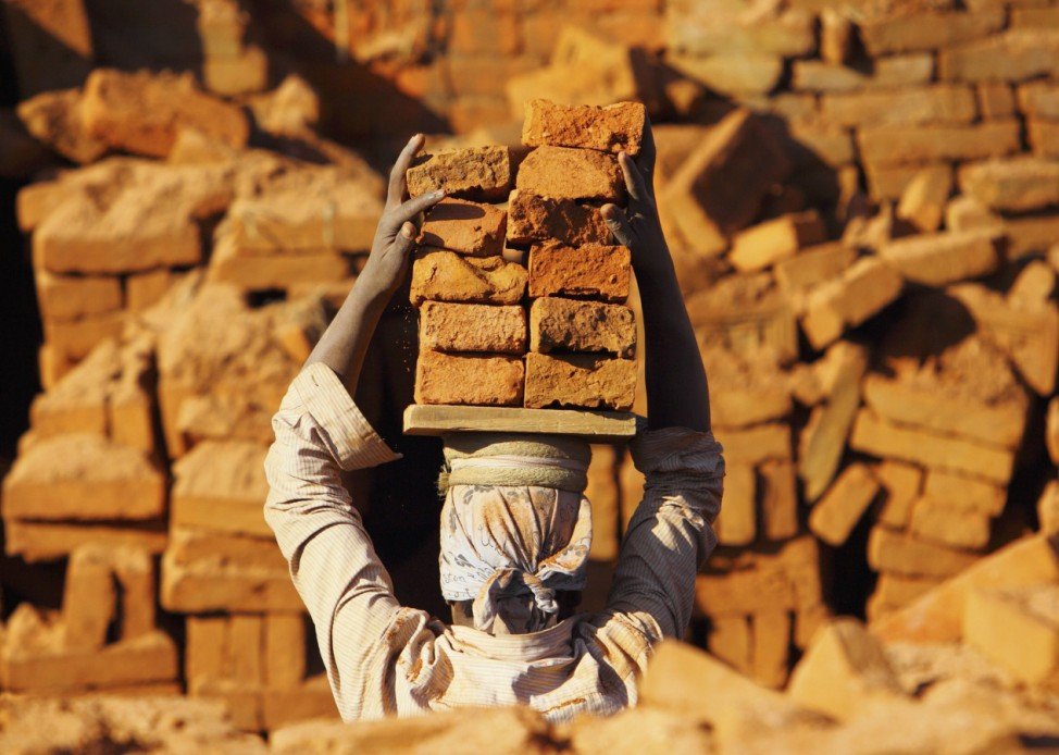 A worker carries bricks by balancing them on the head at a brick factory in Bhaktapur