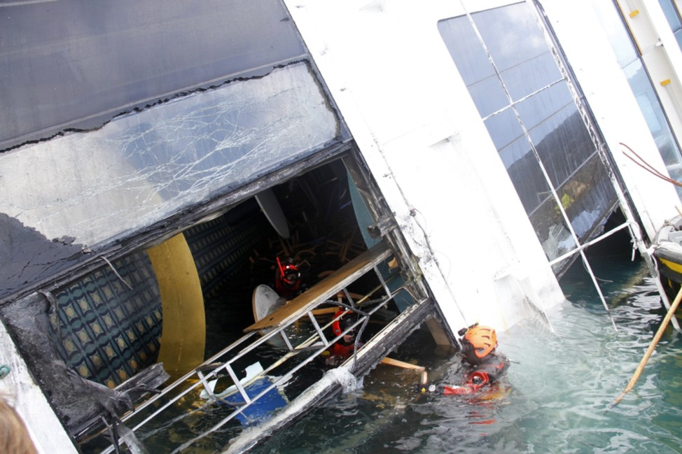 Firefighters work inside the Costa Concordia cruise ship which ran aground off the west coast of Italy at Giglio island