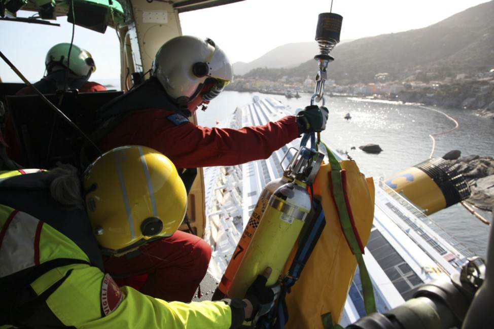 Firefighters hang scuba equipment in a chopper over the Costa Concordia cruise ship which ran aground off the west coast of Italy at Giglio island