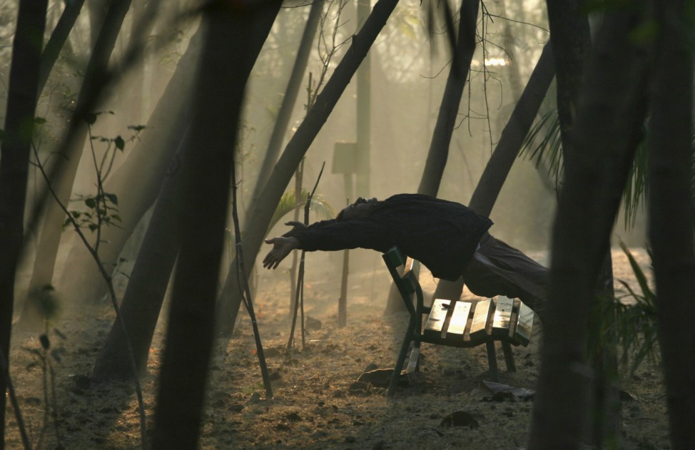 A morning jogger stretches in a park on a cold winter day on the outskirts of New Delhi