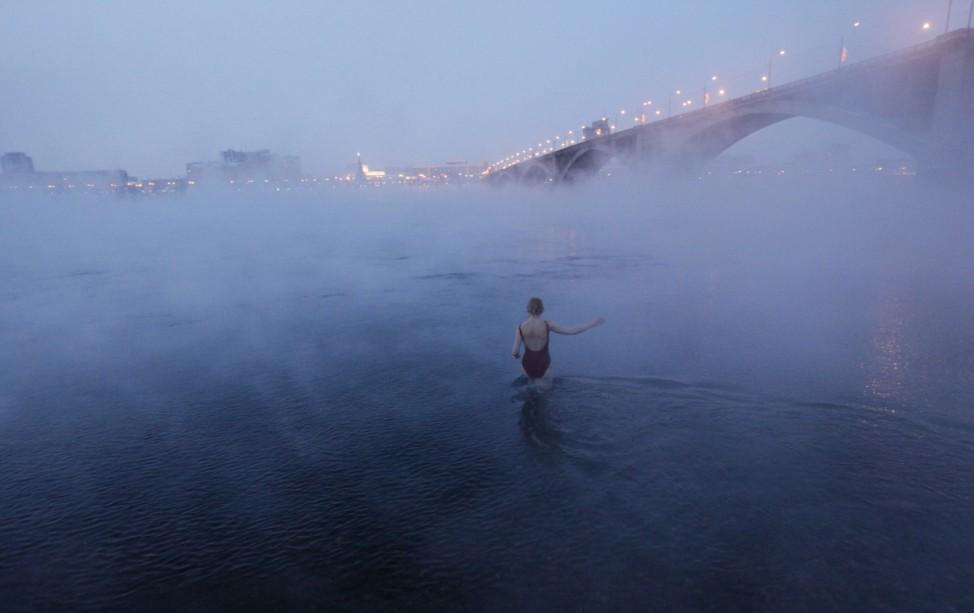 Member of the Cryophil amateur winter bathing club enters the Yenisei River at air temperature some minus 26 Celcius in Krasnoyarsk