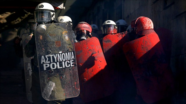 Greek police officers, some covered in red paint thrown by anti-austerity protesters, stand next to the parliament during clashes in Athens