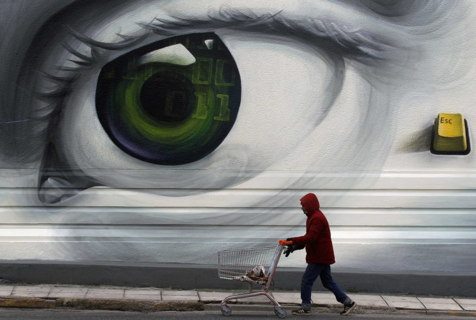An immigrant pushes an empty shopping trolley past graffiti in Athens