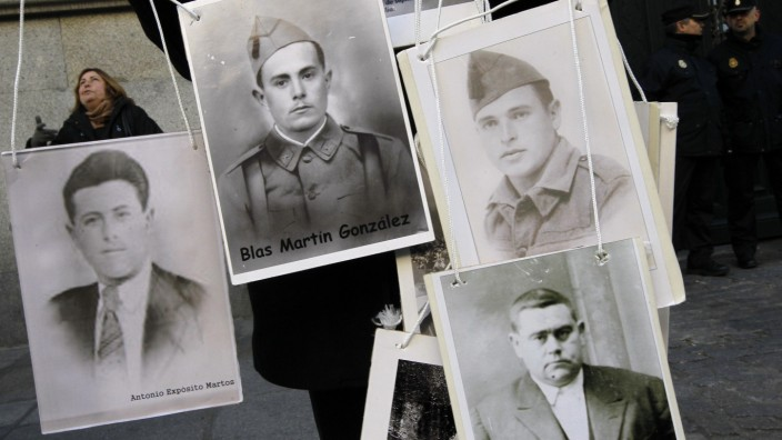 A supporter of Spanish judge Baltasar Garzon shows photos of Francoism victims during a protest outside Madrid's Supreme Court