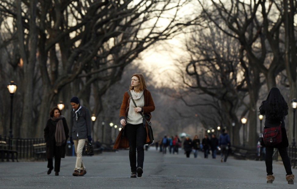 The last rays of sunshine fall on pedestrians as they walk through Central Park on an unseasonably warm day in New York