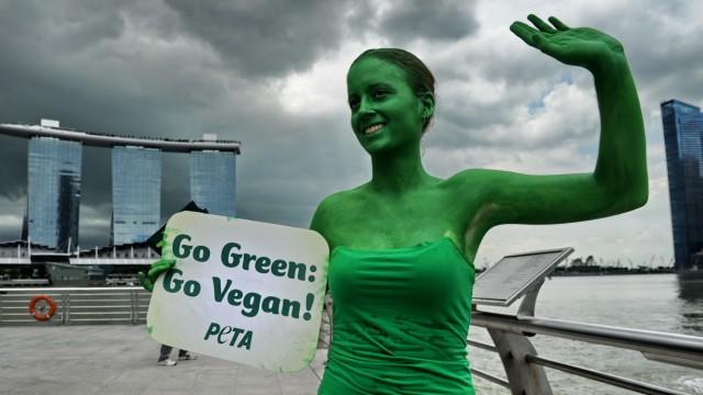 Psychologie und Ernährung: Eine Peta-Anhängerin demonstriert in Singapur für eine vegane Lebensweise: Fleischverweigerer lösen bei Fleischessern Abwehrreaktionen aus.