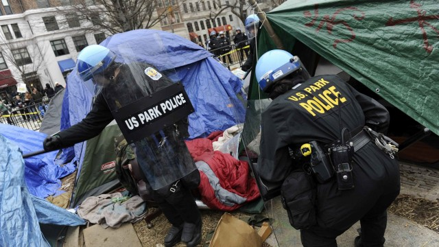 U.S. National Park Service police inspect empty tents as they seal off the Occupy DC encampment in McPherson Square in Washington
