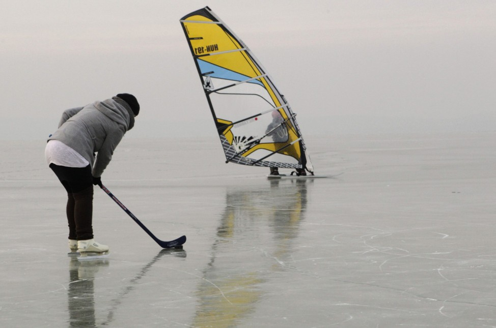 A person plays ice hockey next to an ice surfer on a frozen Neusiedlersee in Podersdorf
