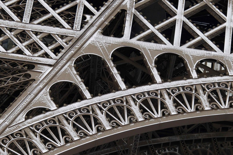Freshly fallen snow is seen on the iron work of the Eiffel Tower in Paris as sub-freezing winter temperatures continue