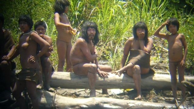 Members of the Mashco-Piro tribe observe an expedition of the Spanish Geographical Society from across the Alto Madre de Dios river