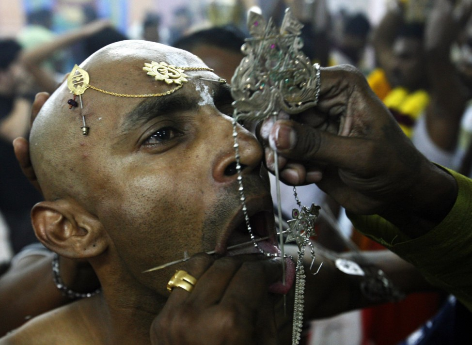A devotee has his tongue pierced during Thaipusam festival in Singapore