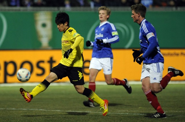 Holstein Kiel's Berzel and Borussia Dortmund's Kagawa fight for the ball during their quarter final German soccer cup (DFB-Pokal) match in Kiel.