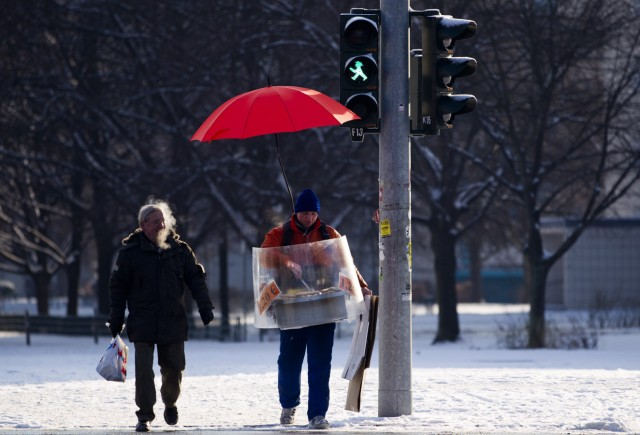A sausage vendor carrying a portable grill stands at a traffic light in Berlin