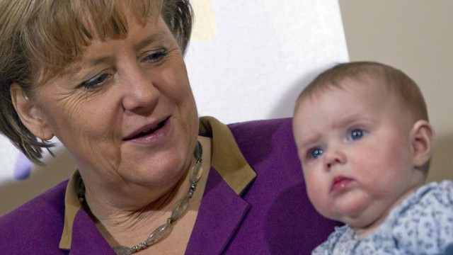 Kanzlerin Merkel mit einem Baby auf einer Veranstaltung.