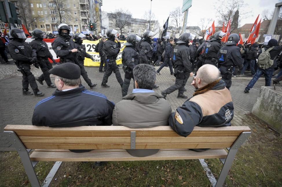 Men watch German riot police walking alongside left-wing anti neo-Nazis march in Dresden