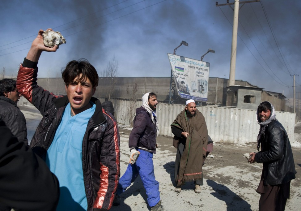 Afghan protesters hold rocks during a protest near a U.S. military base in Kabul