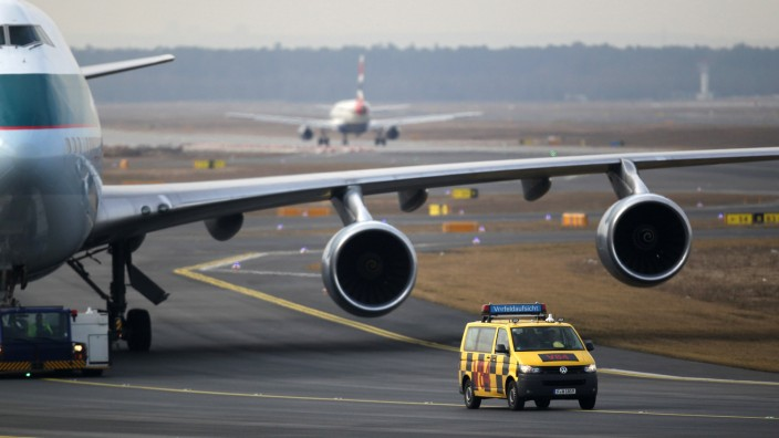 Airport controller vehicle is pictured in front of a Cathay Pacific Boeing B747-400 Aircraft on runway at Frankfurt's airport