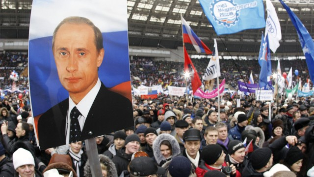 People take part in a rally to support presidential candidate and Russia's current Prime Minister Putin at the Luzhniki stadium on the Defender of the Fatherland Day in Moscow