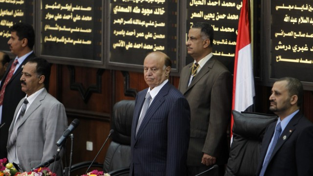 Yemen's newly elected president Hadi stands for the national anthem before taking oath at the parliament in Sanaa