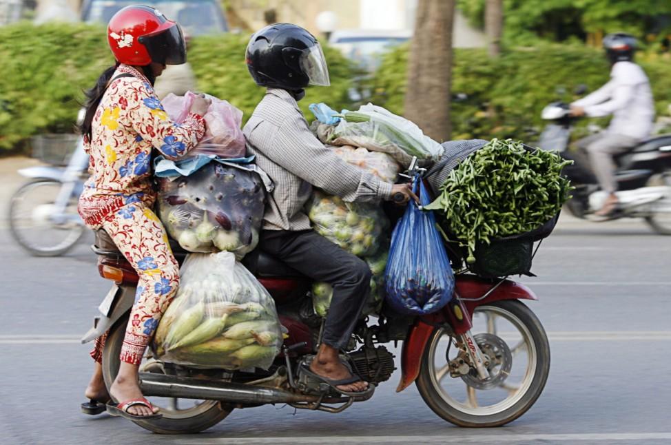 Frau und Mann fahren auf einem Moped in Phnom Penh, Kambodscha