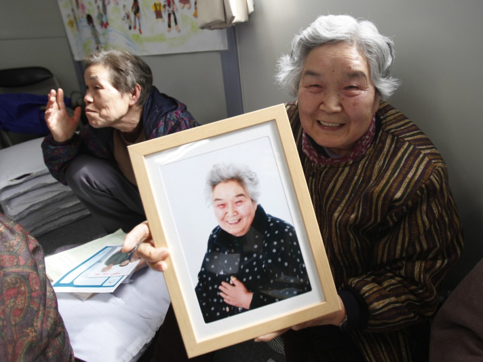 Misako Yokota shows her framed portrait after receiving it from 3.11 Portrait Project volunteers in Koriyama