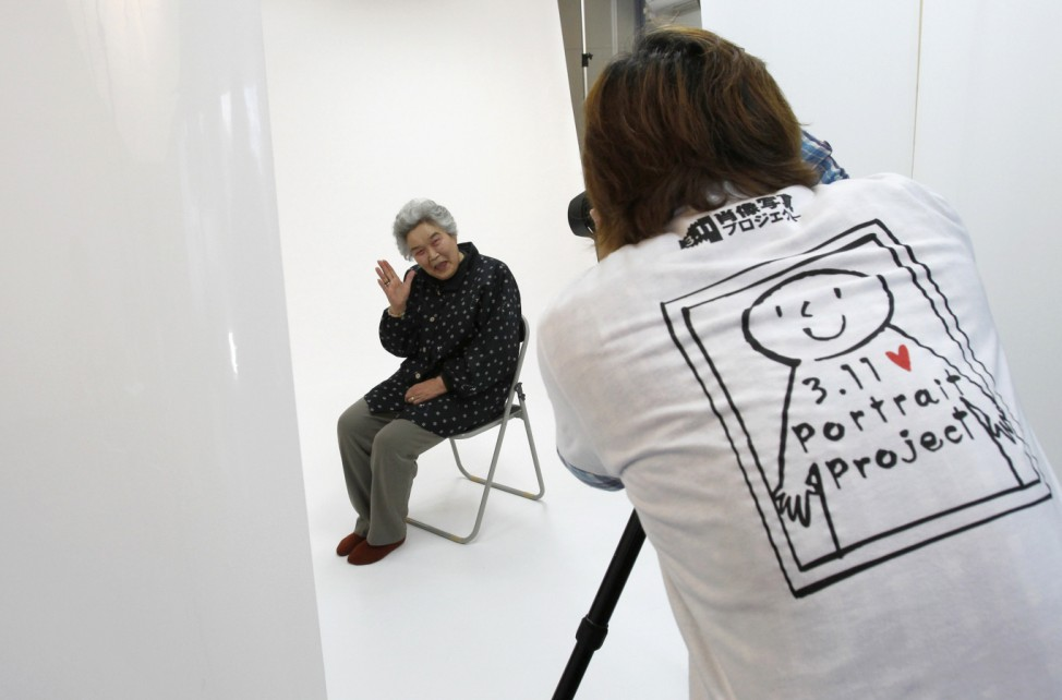 Photographer Kenichi Funada takes a portrait of Misako Yokota as part of the 3.11 Portrait Project in Koriyama