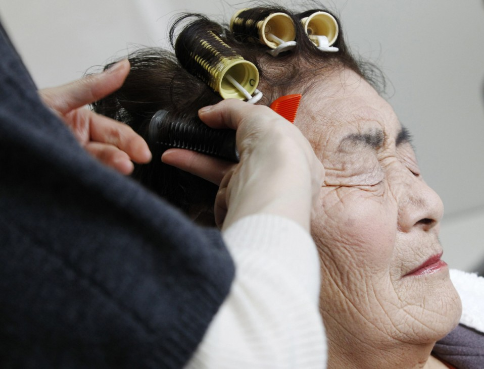 A resident has her hair done by a stylist as part of the 3.11 Portrait Project in Koriyama