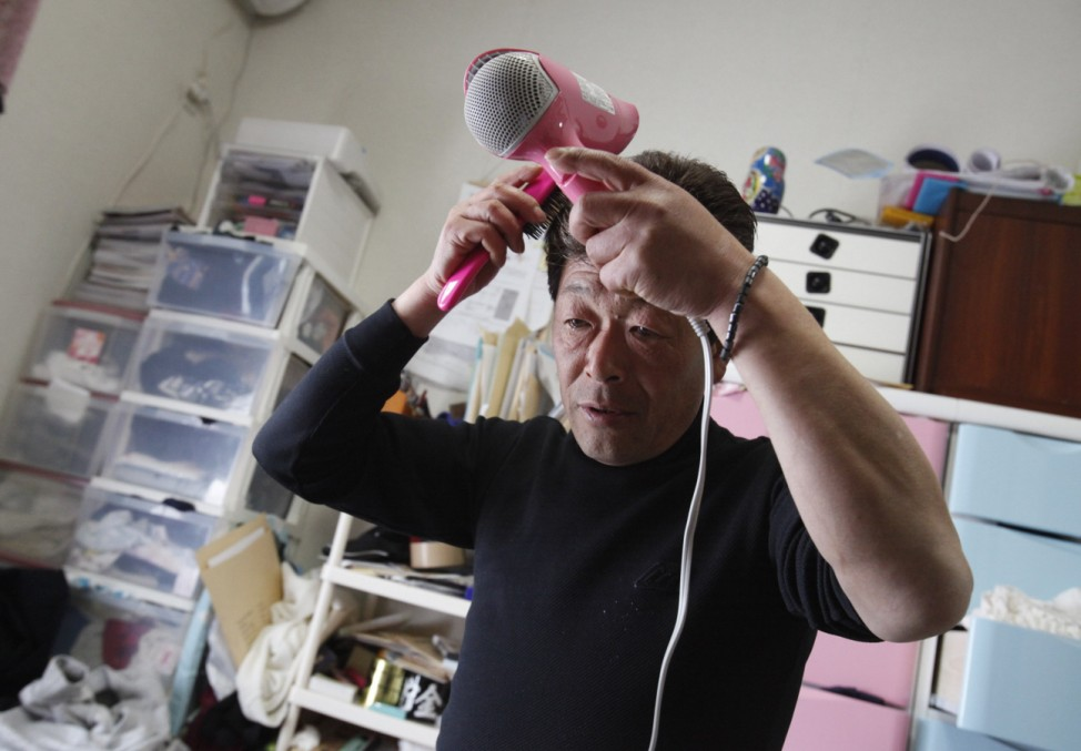 Takaaki Watanabe dries his hair in his temporary home, ahead of a parent's day event for his youngest daughter Manami