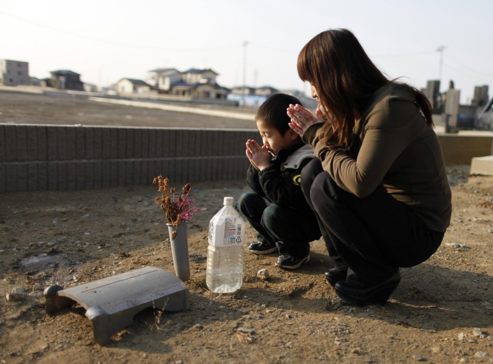 Yuko Sugimoto prays with her son Raito outside their house in Ishinomaki