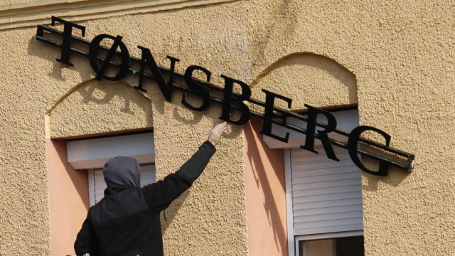 A worker mounts a sign with the new name 'Tonsberg' at a clothing store of the Thor Steiner lable in Chemnitz