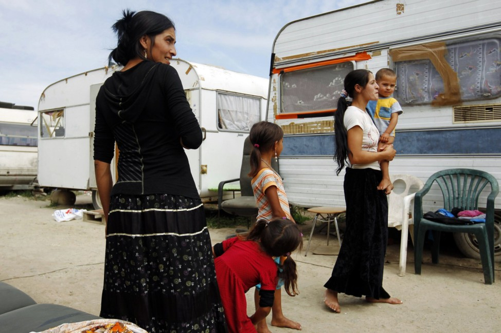 Woman gather near caravans inside an illegal camp of travelling people in Indre, near Nantes