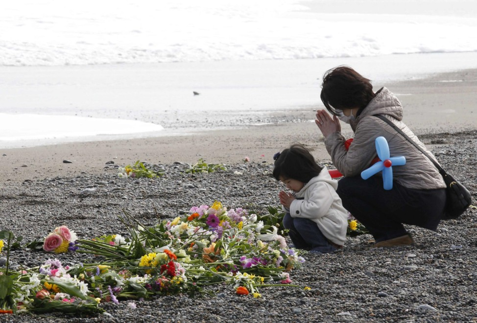 People offer prayers for victims of the March 11, 2011 earthquake and tsunami during the first anniversary of the disaster in Iwaki