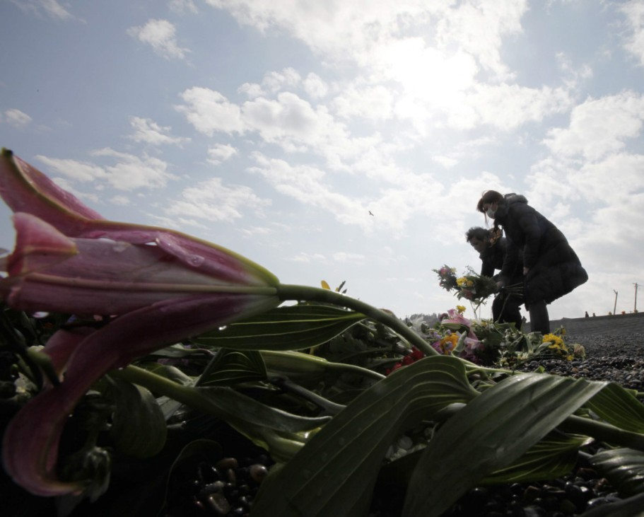 Mourners offer prayers for victims of the March 11, 2011 earthquake and tsunami during the first anniversary of the disaster in Iwaki