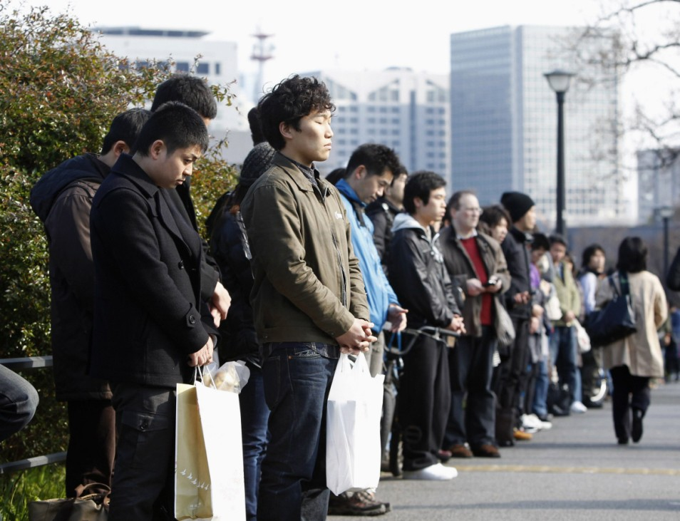People take part in a moment of silence at 2:46 p.m. (0546 GMT) around the Imperial Palace in Tokyo