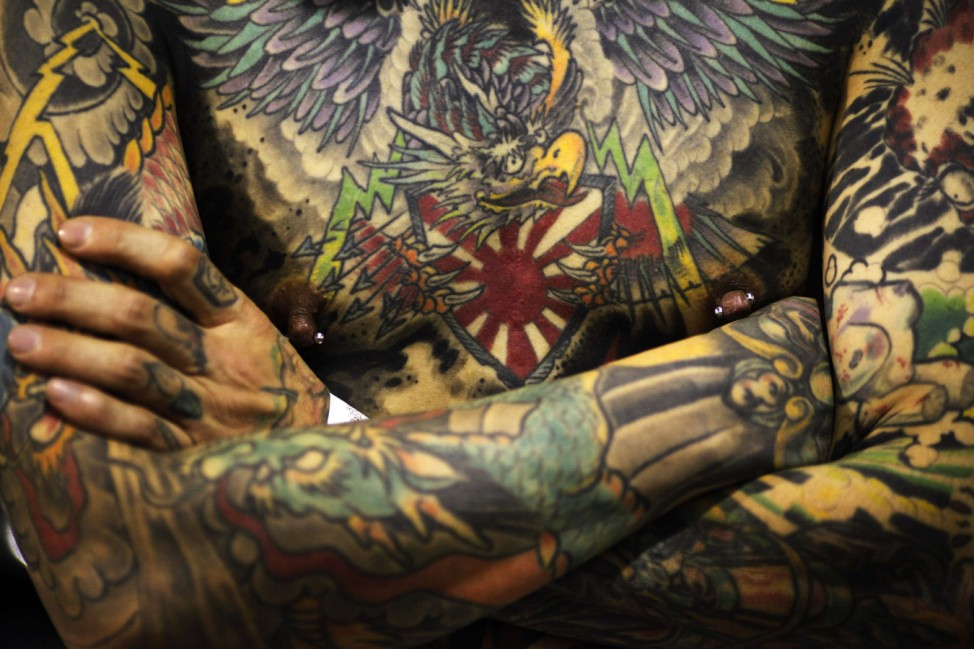 Tattooed man prepares to go on stage during the final day of the Bangkok International Tattoo convention in Bangkok