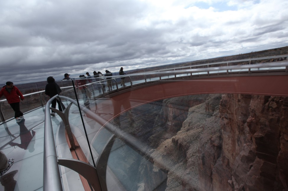 Visitors have a view to the Grand Canyon below from a glass skywalk overlooking the Grand Canyon and the Colorado River, on the Hualapai Indian Reservation, Arizona