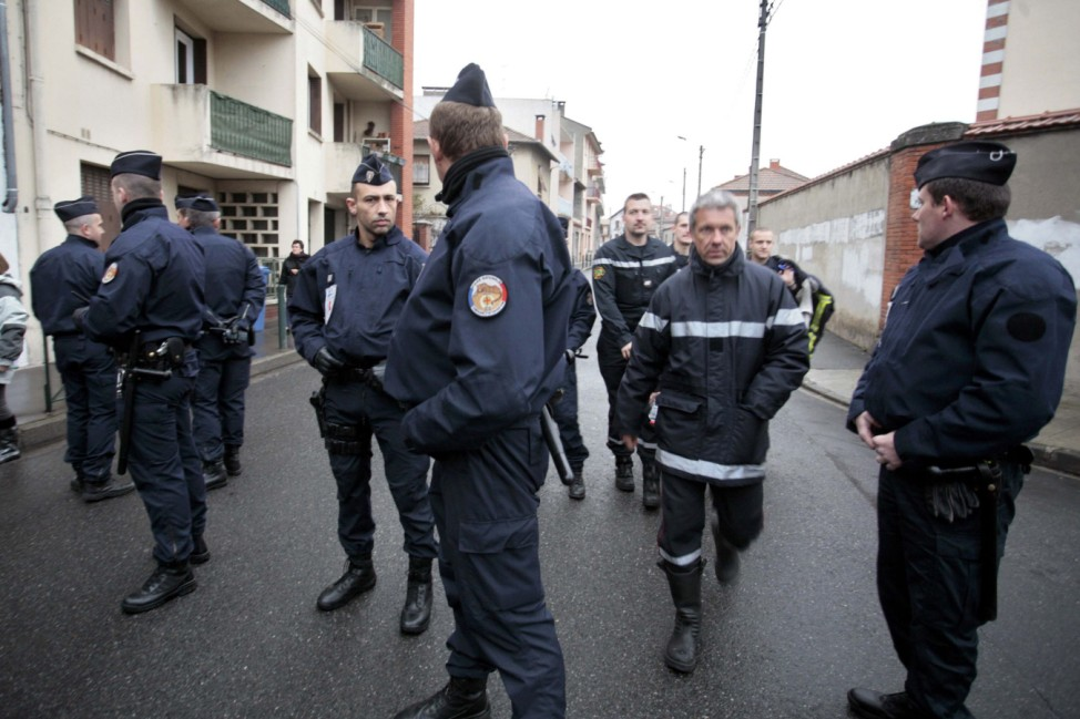 Police forces block a street during a raid on a house to arrest a gunman in Toulouse